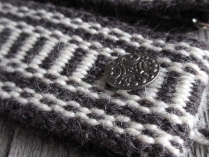 Weaving belt black and white closeup pewter button